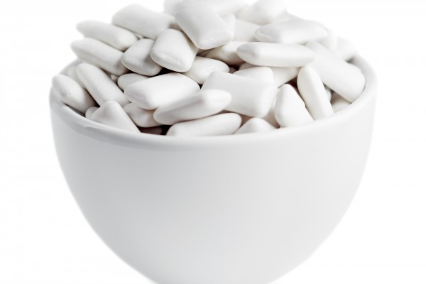 <p>Small white bowl of white rectangular chewing gum isolated on white.</p>